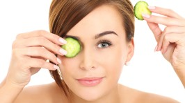 A picture of a face of a beautiful woman posing with a cucumber over white background